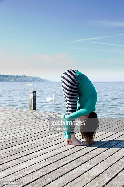 side view of mature woman on pier by ocean bending over holding ankles - older woman bending over stock pictures, royalty-free photos & images