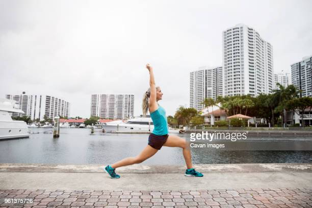 side view of mature woman practicing yoga in warrior i pose on footpath - aventura florida stock photos and pictures