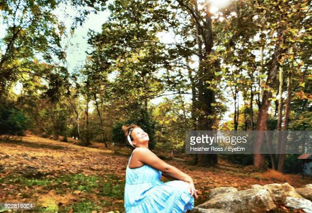 Side View Of Mature Woman Sitting On Field In Forest