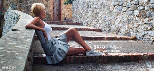 Side View Of Mature Woman Sitting On Steps