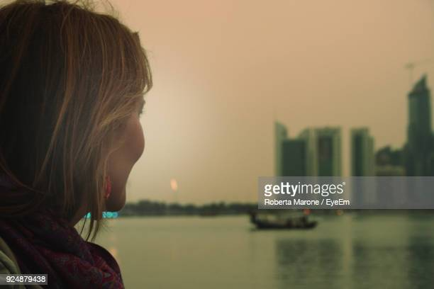 Side View Of Mature Woman Standing By River Against Sky At Sunset