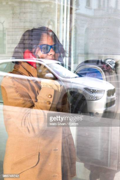 Side View Of Mature Woman Talking On Telephone Seen Through Window
