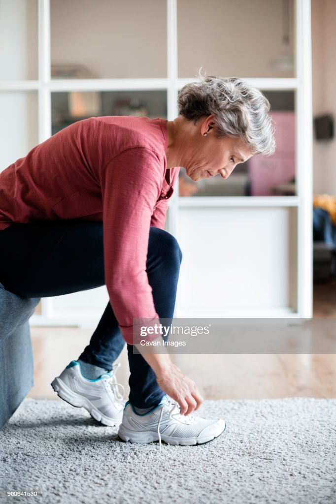 Side view of mature woman tying shoelace at home : Stock Photo