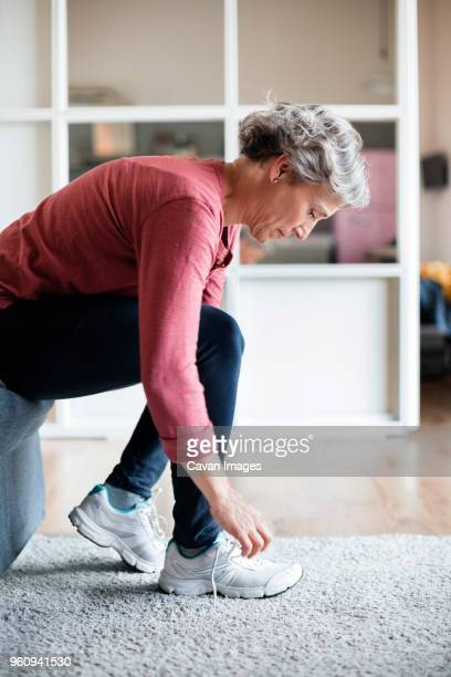 side view of mature woman tying shoelace at home - tie stock pictures, royalty-free photos & images