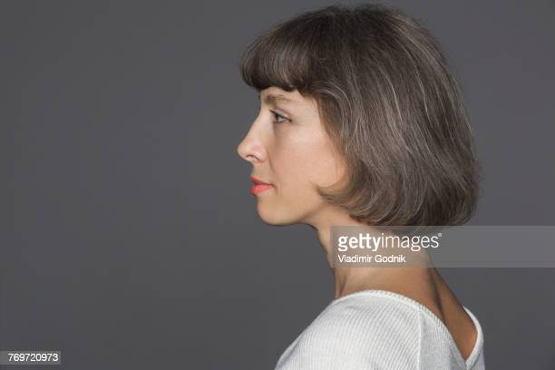 Side view of mature woman with brown hair against gray background