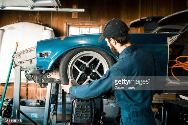 side view of mechanic repairing car in workshop - vintage auto repair stock pictures, royalty-free photos & images