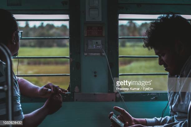 side view of men sitting in train by windows - karnataka stock pictures, royalty-free photos & images