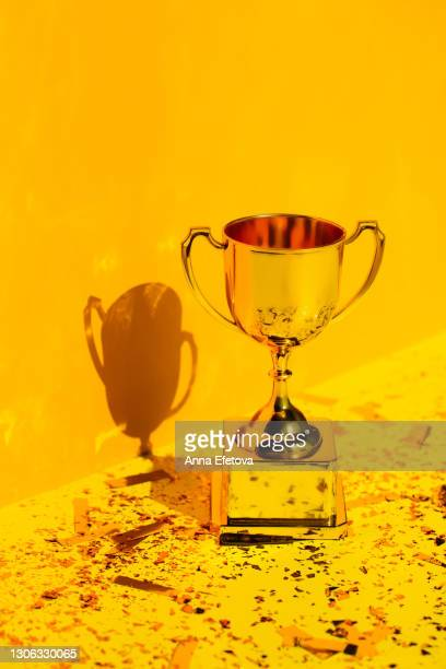 side view of metallic golden goblet on bright yellow table with sequin near yellow wall with shadow. goal achievement concept. trendy colors of the year - trophy stock pictures, royalty-free photos & images
