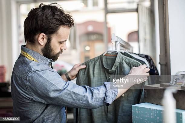 Side view of mid adult male design professional analyzing shirt at studio