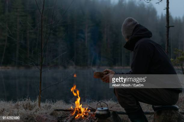 side view of mid adult man camping in forest during winter at dusk - 焚き火 ストックフォトと画像