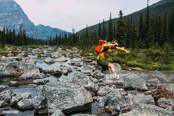 side view of mid adult man carrying backpack jumping over rocky riverbed, moraine lake, banff national park, alberta canada - flussbett stock-fotos und bilder