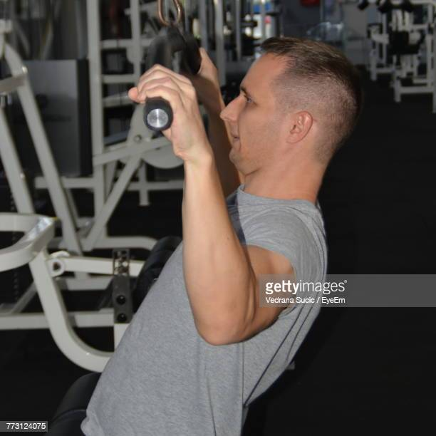 Side View Of Mid Adult Man Exercising In Gym