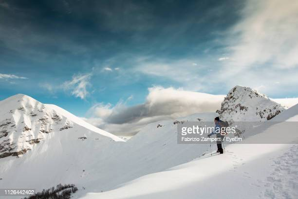 side view of mid adult man hiking on snowcapped mountain against cloudy sky - fabrizio zampetti foto e immagini stock