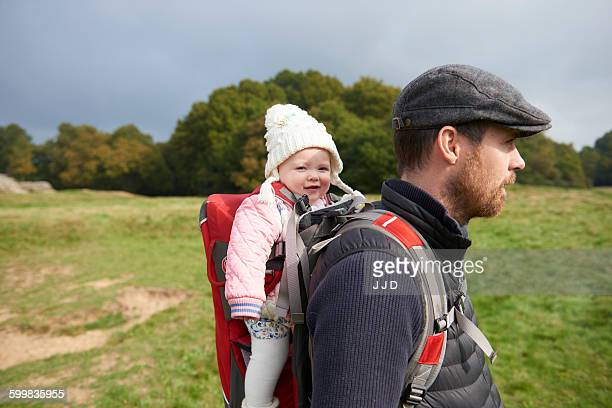Side view of mid adult man in field wearing flat cap carrying daughter on back in baby carrier
