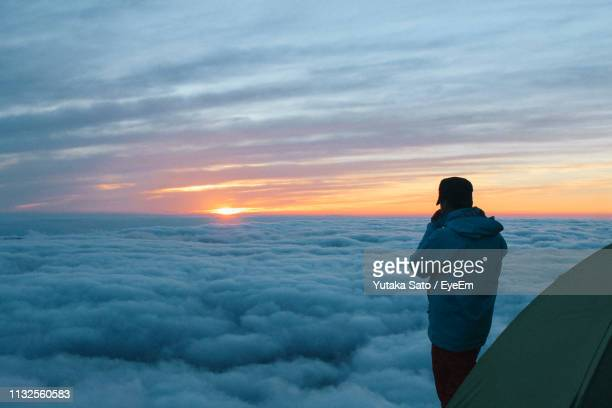 side view of mid adult man looking at cloudscape while camping on mountain during sunset - 長野県 ストックフォトと画像