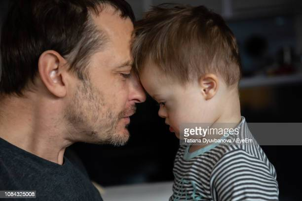 side view of mid adult man looking at son with down syndrome - pessoas com deficiência imagens e fotografias de stock