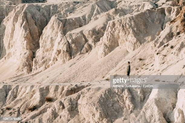 side view of mid adult man standing on mountain during sunny day - adriana duduleanu stock photos and pictures