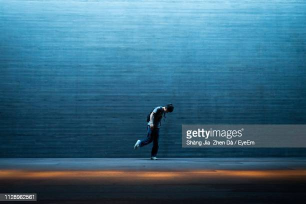 side view of mid adult man standing on road against wall at night - leben in der stadt stock-fotos und bilder