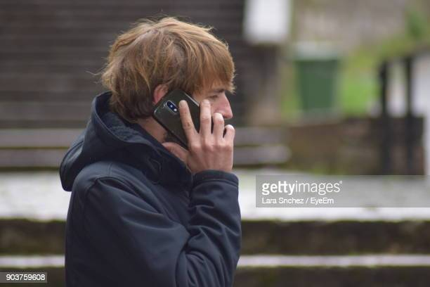 Side View Of Mid Adult Man Talking On Mobile Phone While Standing Outdoors