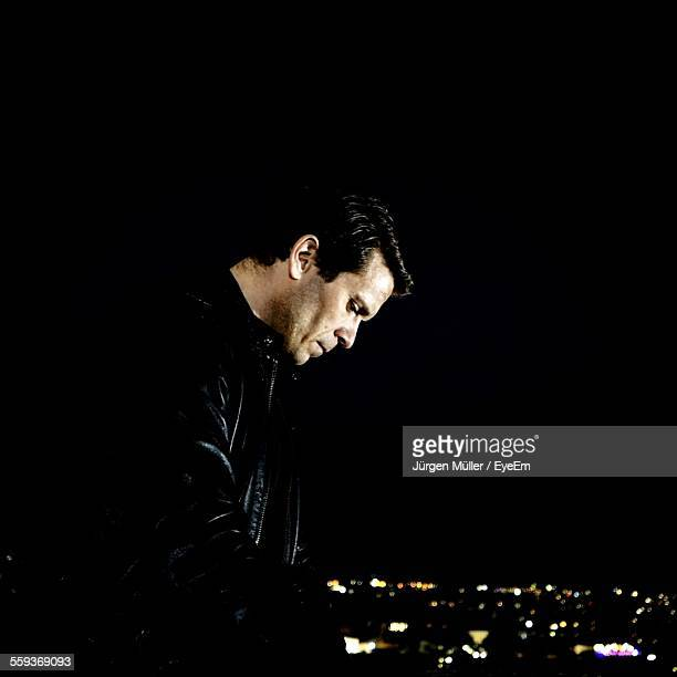 side view of mid adult man wearing leather jacket looking down at night - giacca nera foto e immagini stock