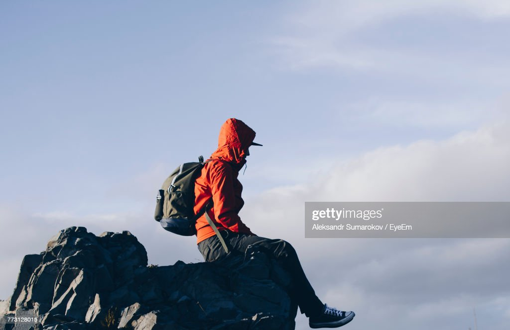 Side View Of Mid Adult Man With Backpack Sitting On Rock Formation Against Cloudy Sky : Photo