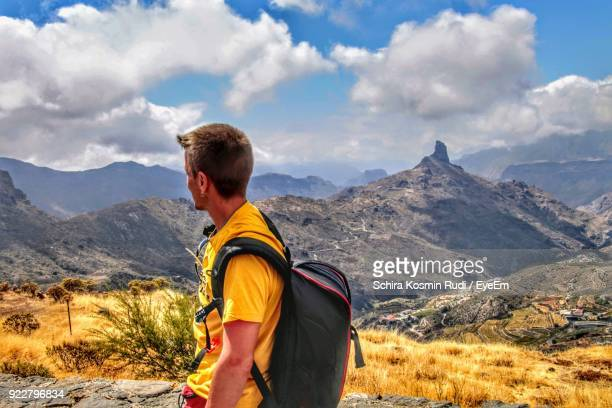 Side View Of Mid Adult Man With Backpack Standing On Mountain Against Sky