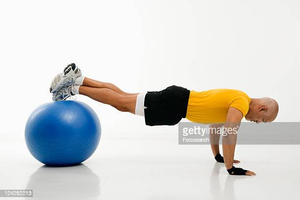 side view of mid adult multiethnic man doing pushups while balancing on blue exercise ball. - blue balls pics stock pictures, royalty-free photos & images