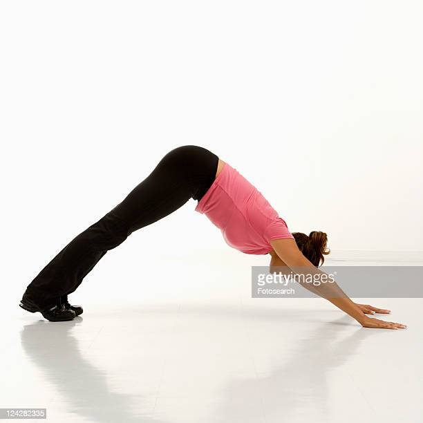 Side view of mid adult multiethnic woman wearing exercise clothing in downward dog yoga pose.