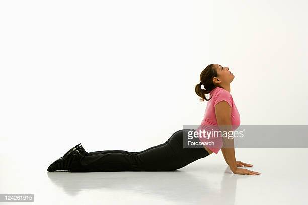 Side view of mid adult multiethnic woman wearing exercise clothing holding cobra yoga pose.