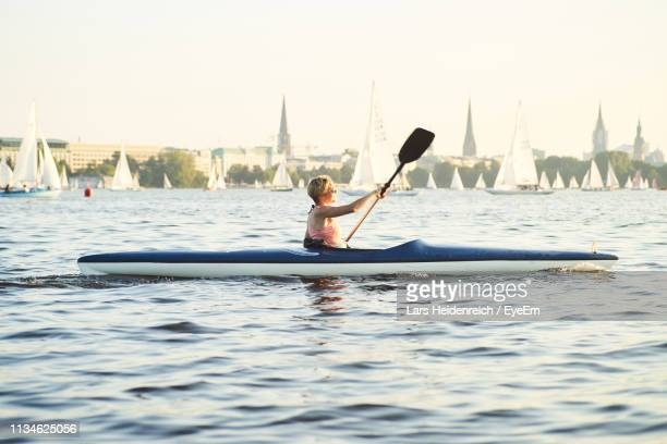 side view of mid adult woman canoeing on sea against clear sky during sunset - kanu stock-fotos und bilder