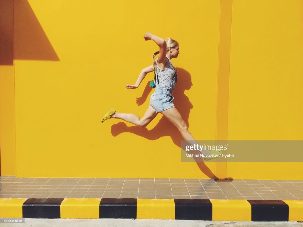 Side View Of Mid Adult Woman Jumping On Footpath Against Yellow Wall : Stock Photo