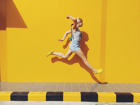 Side View Of Mid Adult Woman Jumping On Footpath Against Yellow Wall - gettyimageskorea