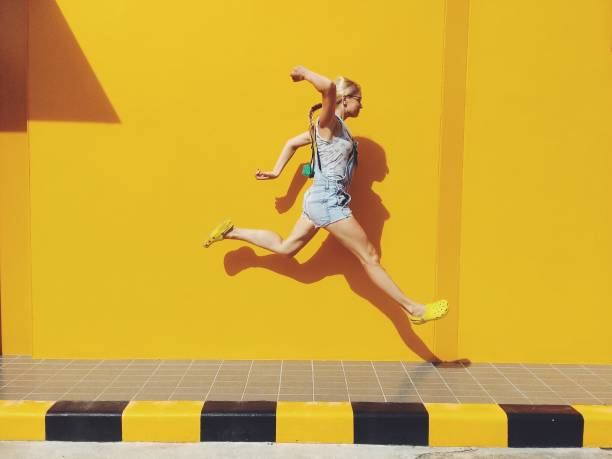 side view of mid adult woman jumping on footpath against yellow wall - 彩色影像 個照片及圖片檔