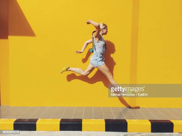 side view of mid adult woman jumping on footpath against yellow wall - kleurenfoto stockfoto's en -beelden