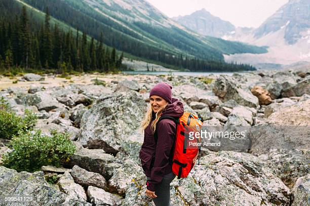 Side view of mid adult woman on rocky landscape carrying backpack looking at camera smiling, Moraine Lake, Banff National Park, Alberta Canada