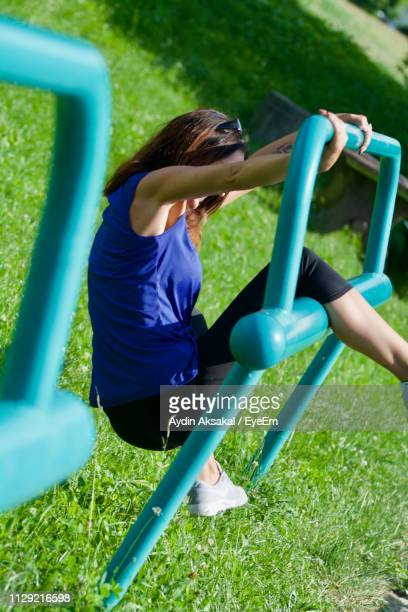 Side View Of Mid Adult Woman Playing On Outdoor Play Equipment In Park