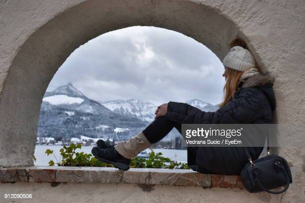 Side View Of Mid Adult Woman Sitting On Retaining Wall Against Cloudy Sky