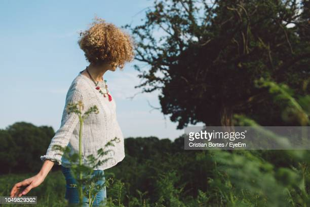 side view of mid adult woman standing by trees and plants on field - bortes stockfoto's en -beelden
