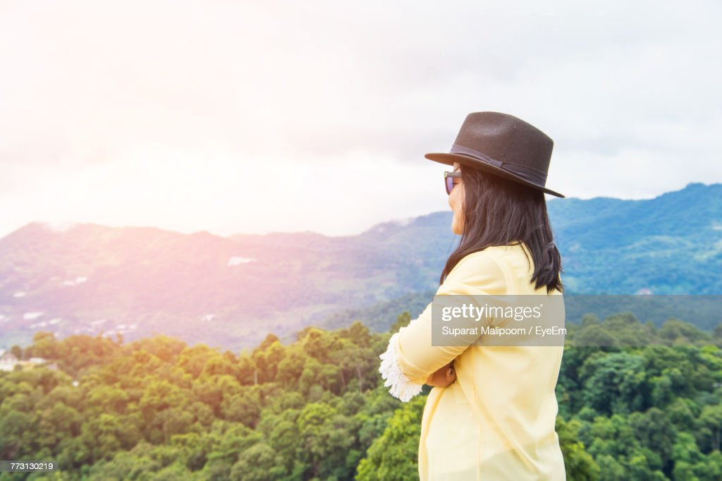 Side View Of Mid Adult Woman Standing On Mountain Against Sky : Photo