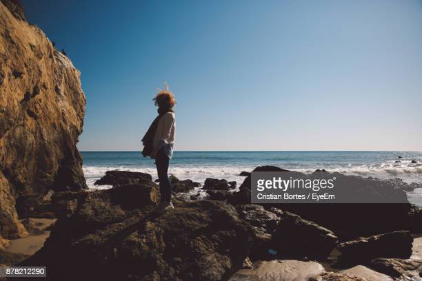 side view of mid adult woman standing on rocky shore against sky - bortes stockfoto's en -beelden