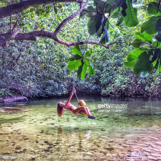 Side View Of Mid Adult Woman Swinging Over Lake In Forest