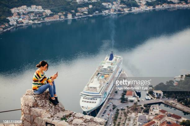side view of mid adult woman using mobile phone while sitting on rock against sea - kreuzfahrt stock-fotos und bilder