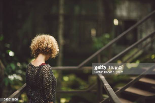 side view of mid adult woman with curly hair standing by railing - bortes stock-fotos und bilder