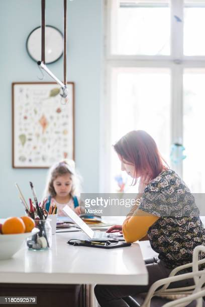 side view of mid adult women working on laptop while sitting with girl at kitchen island - homeschool stock pictures, royalty-free photos & images