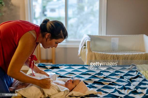 side view of mom drying baby wrapped in towel on bed - nanny stock pictures, royalty-free photos & images