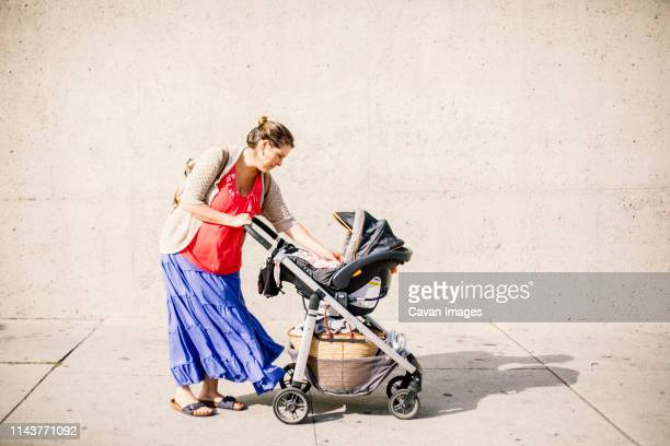 side view of mom who stop in street to take care of baby in stroller - baby stroller stock pictures, royalty-free photos & images