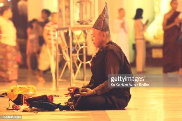 side view of monk meditating while sitting on floor - ko ko htike aung stock pictures, royalty-free photos & images