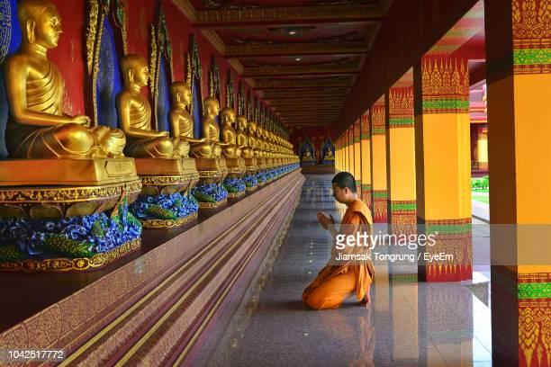 side view of monk praying buddha statues in temple - buddismo foto e immagini stock