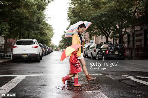 Side view of mother and daughter holding umbrellas while crossing road