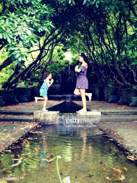 Side View Of Mother And Daughter Standing On One Leg In Prayer Position Amidst Canal At Park
